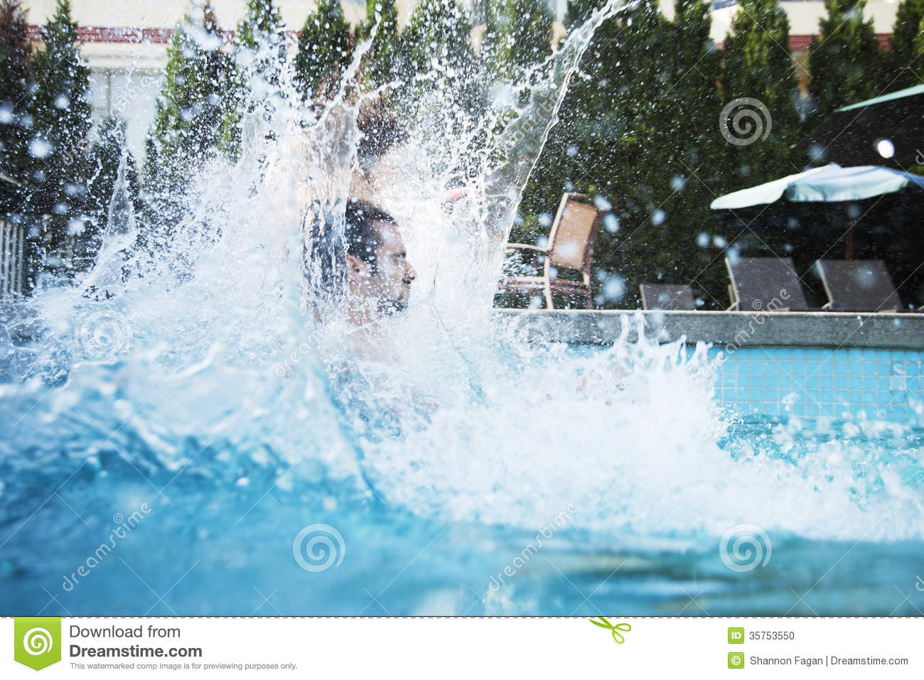 Pool Splash Cannonball young man jumping into a pool with water splashing all around him