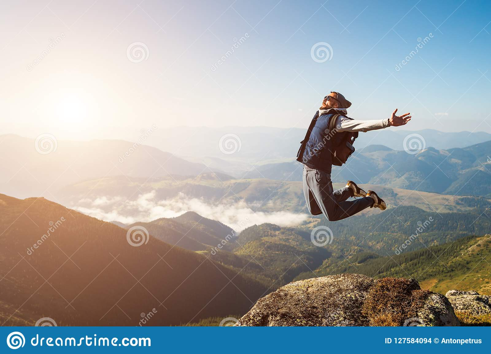 Young man jumping on top of a mountain against the sky