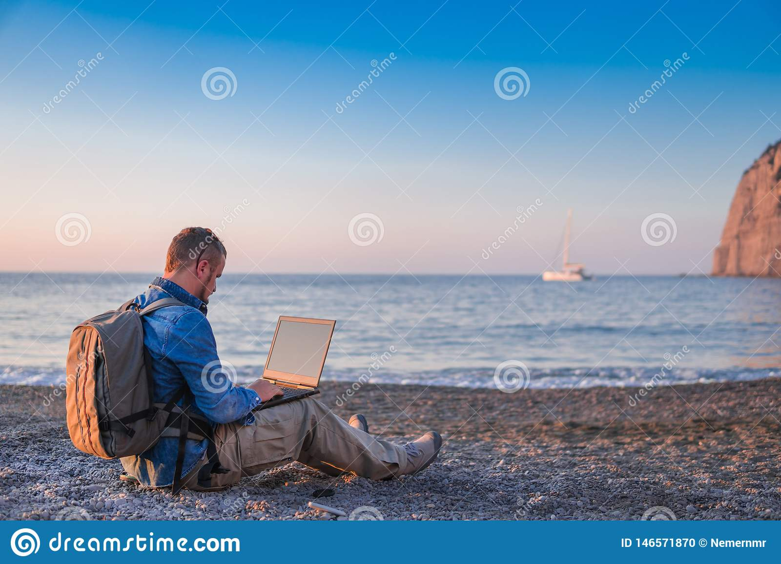 Young man with laptop working on the beach. Freedom, remote work, freelancer, technology, internet, travel and vacation concepts