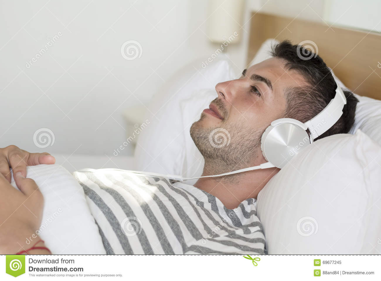 young man laying in bed listening music stock image - image: 69677245