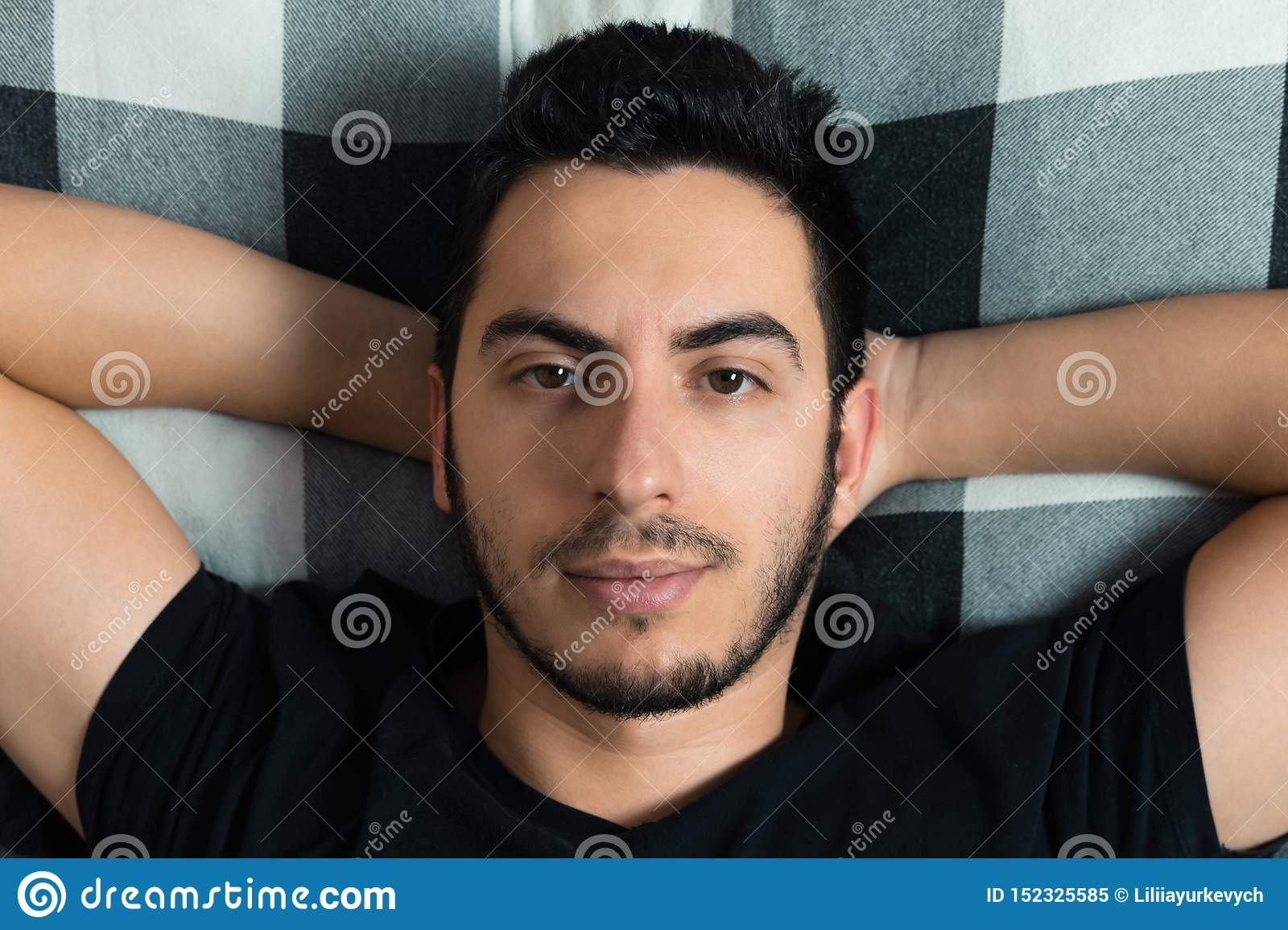 Young man lies in bed
