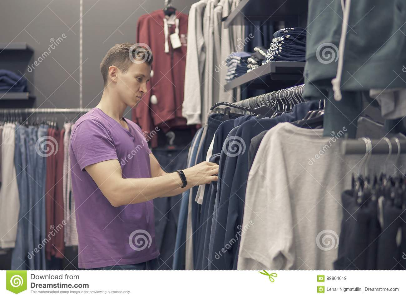 59843d77c Young Man Is Looking For Clothes In The Clothing Shop Stock Image ...