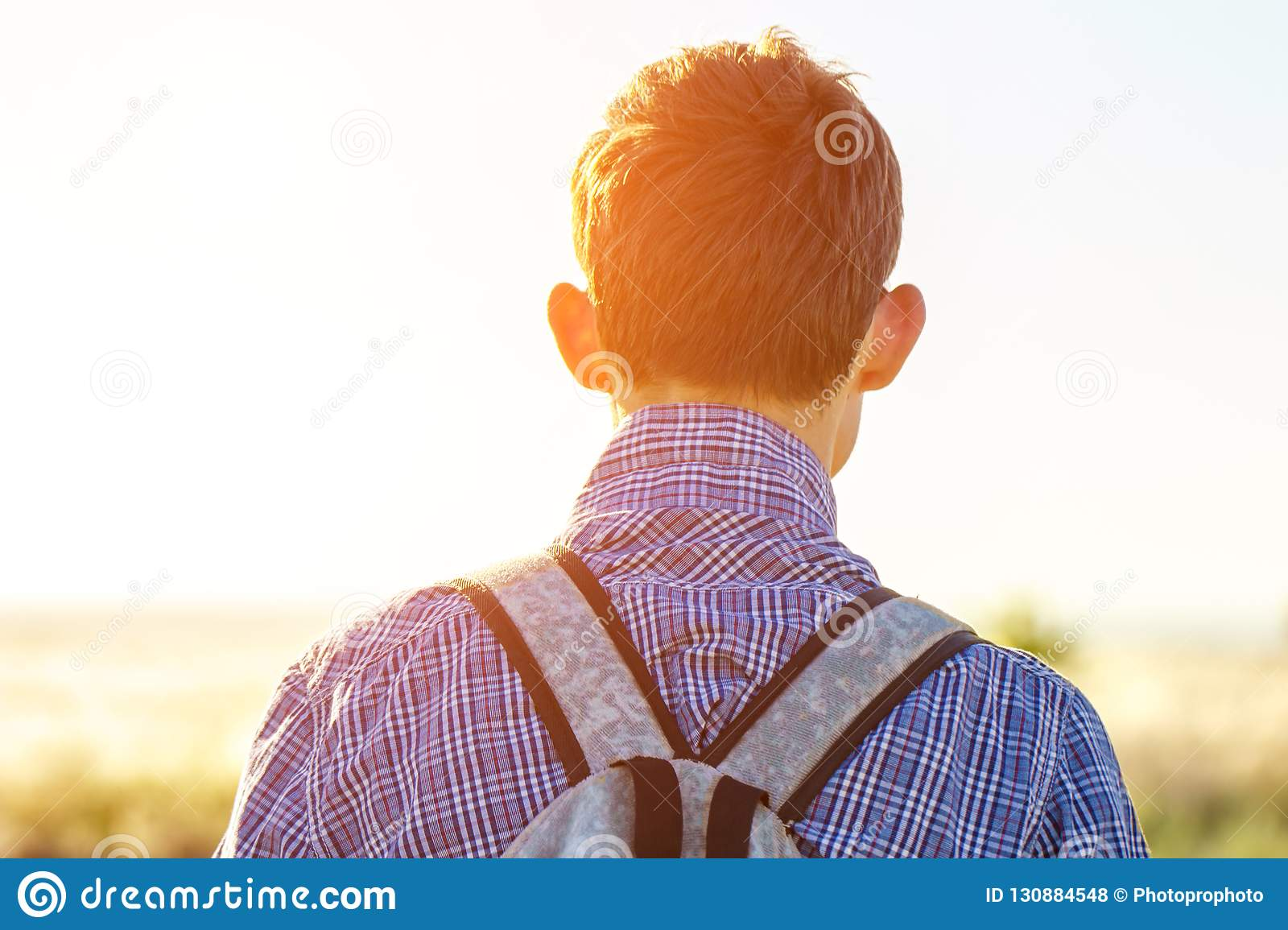 Young man looking into the distance on a Sunny day concept of freedom and tourism