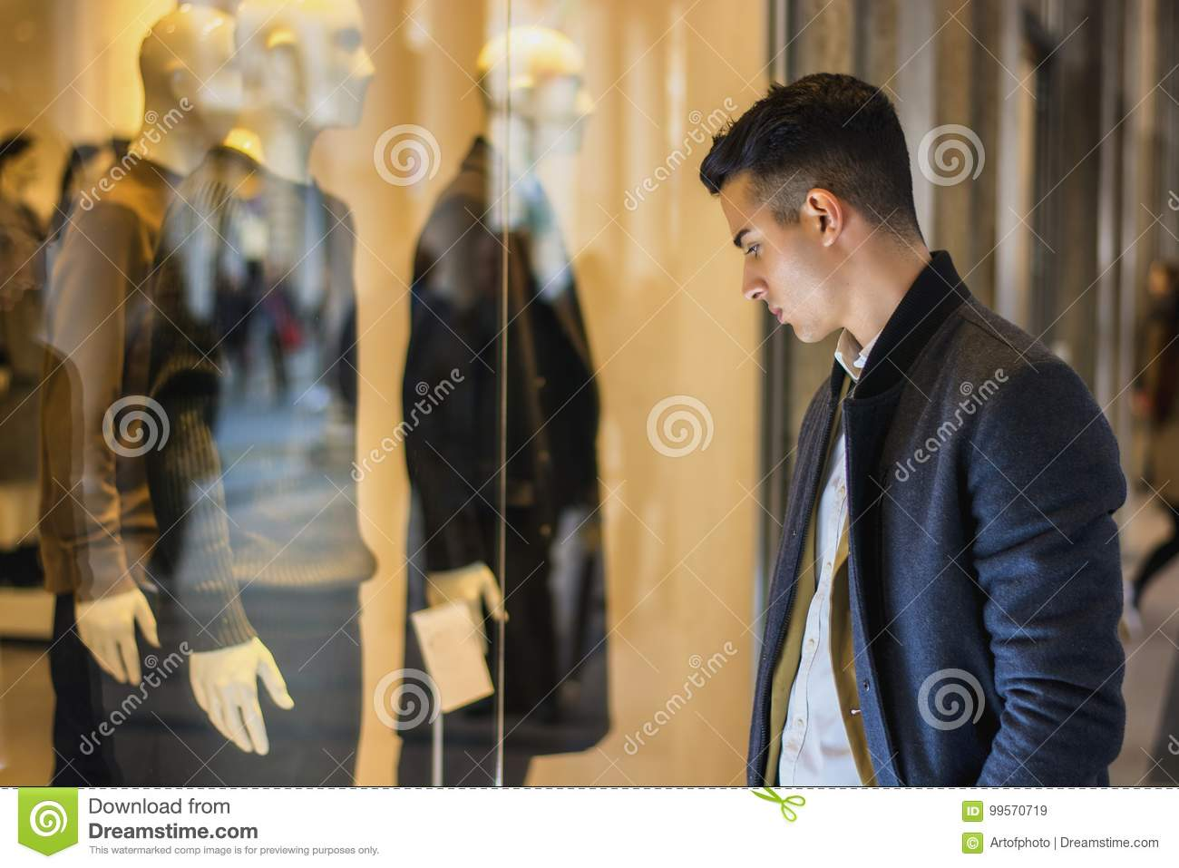 d5aa718a9 Handsome Young Man in Black Elegant Suit Looking at Displayed Fashion Items  in Glass Window Boutique at the High Street Side.