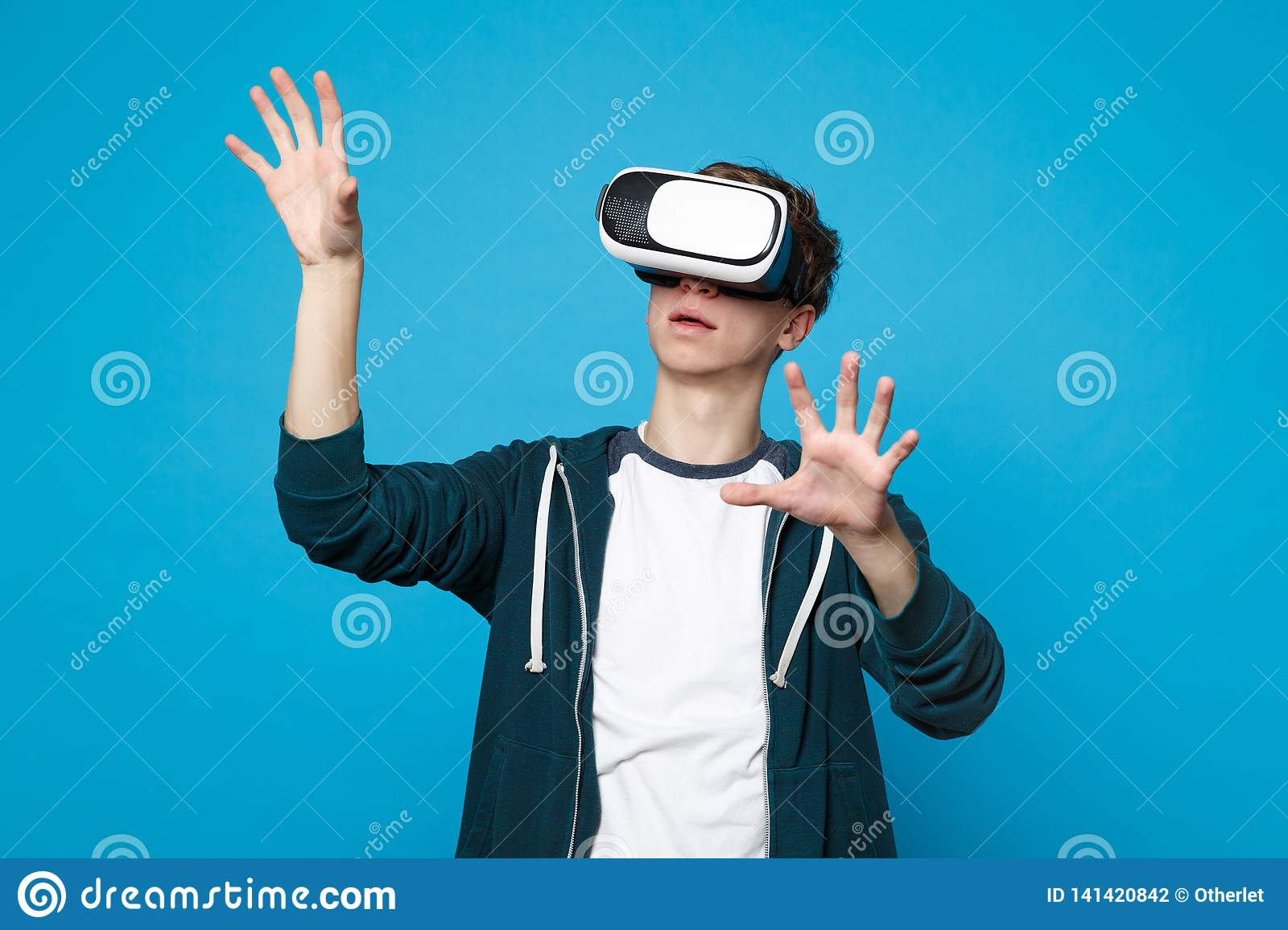 Young man looking on headset touch something like push click on button, pointing at floating virtual screen isolated on