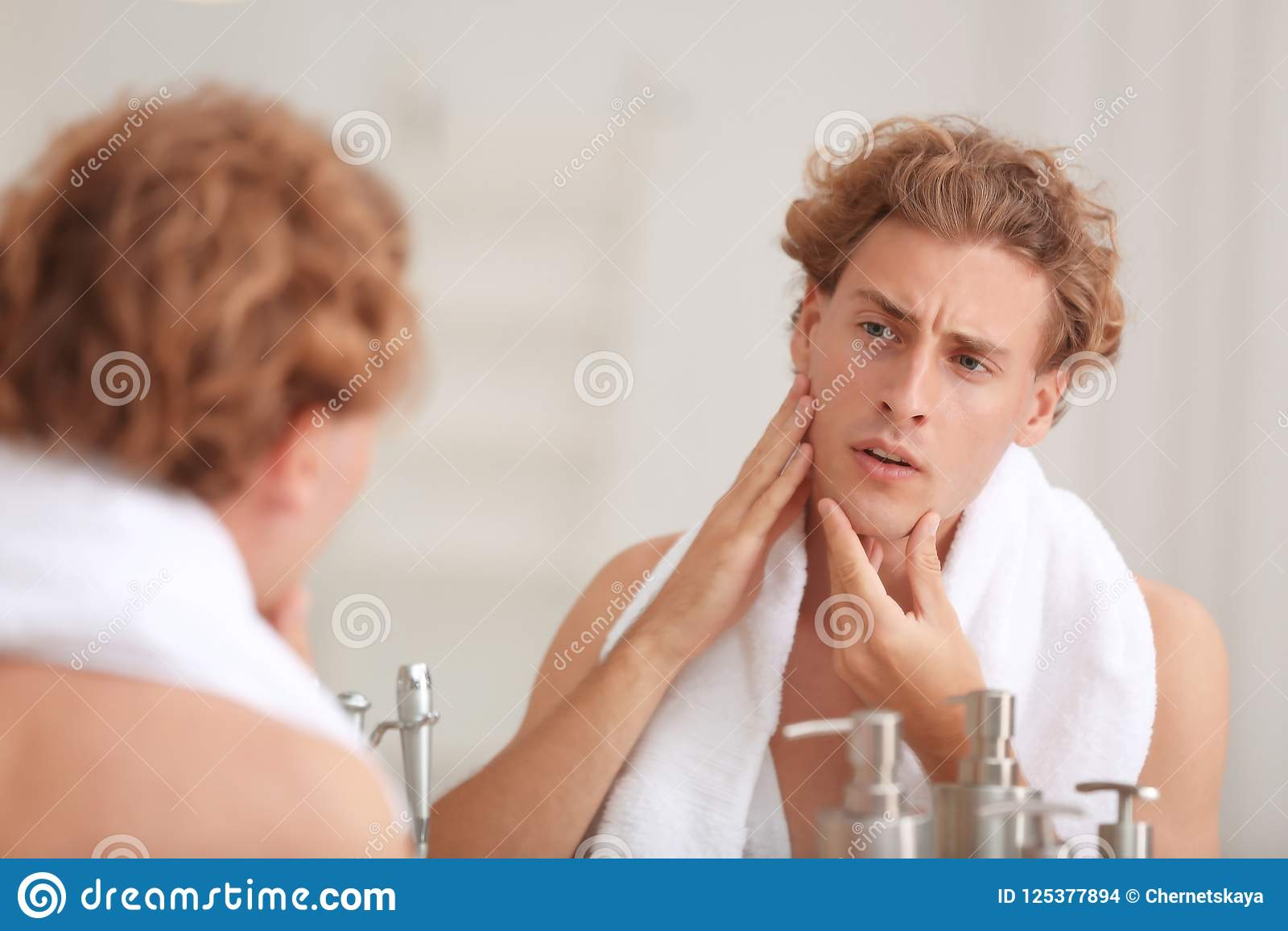 young man looking in mirror after shaving stock photo image of