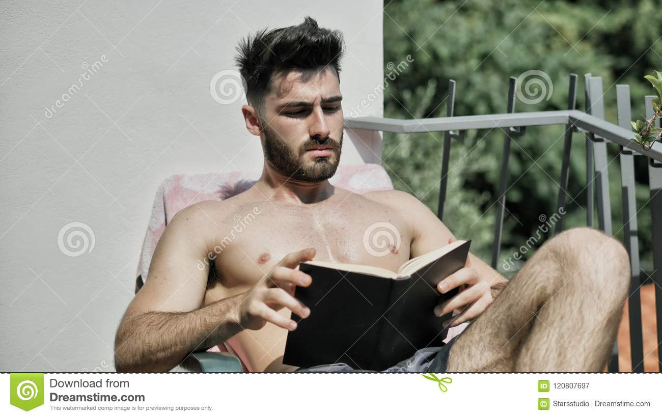 f0ca68a5f6 Shirtless Young Man Drying Off in Hot Sun Reading a Book, Muscular Man  Wearing Bathing Suit Sunbathing on Beach Lounge Chair