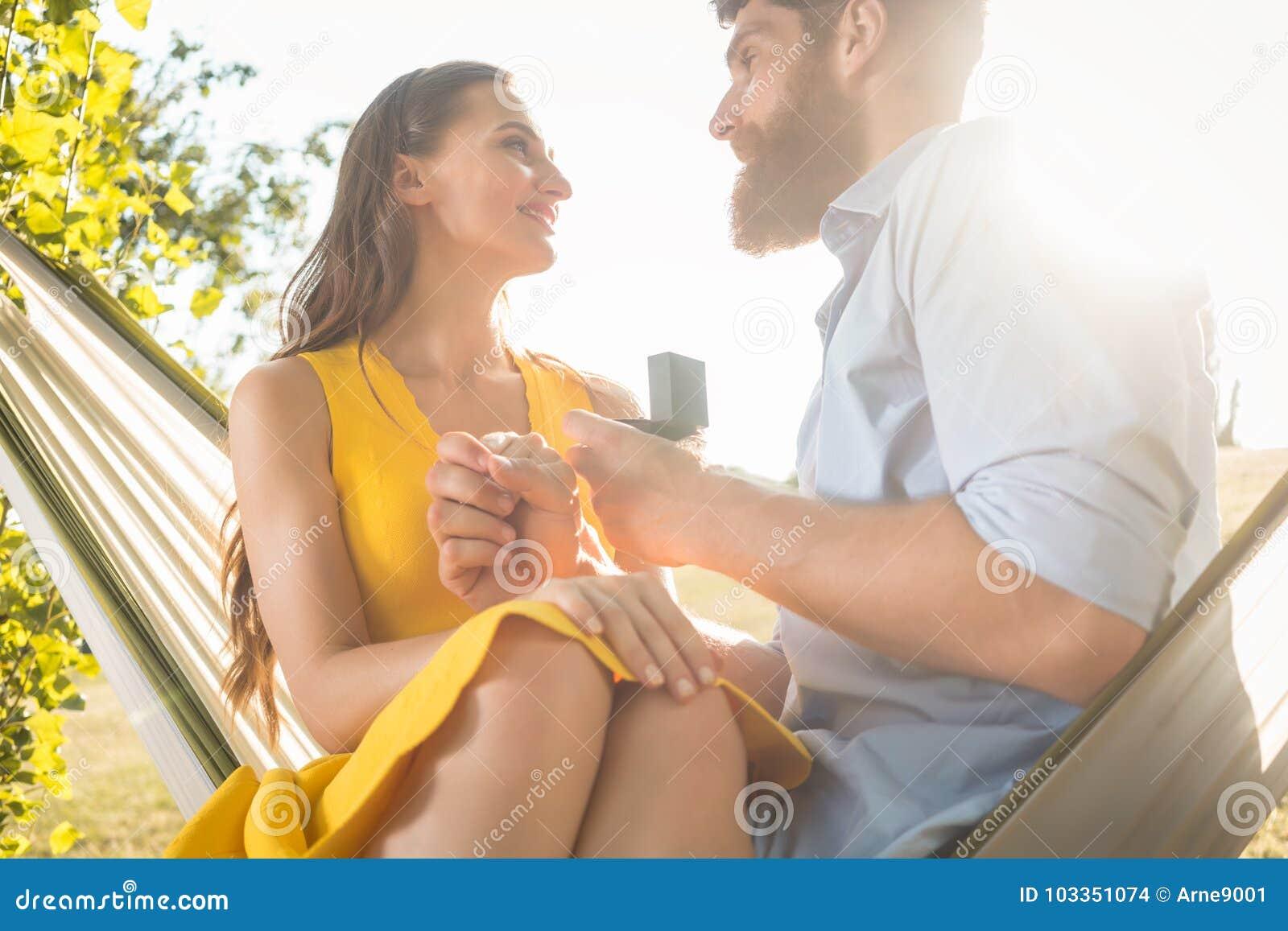 Young man making marriage proposal to beautiful girlfriend while