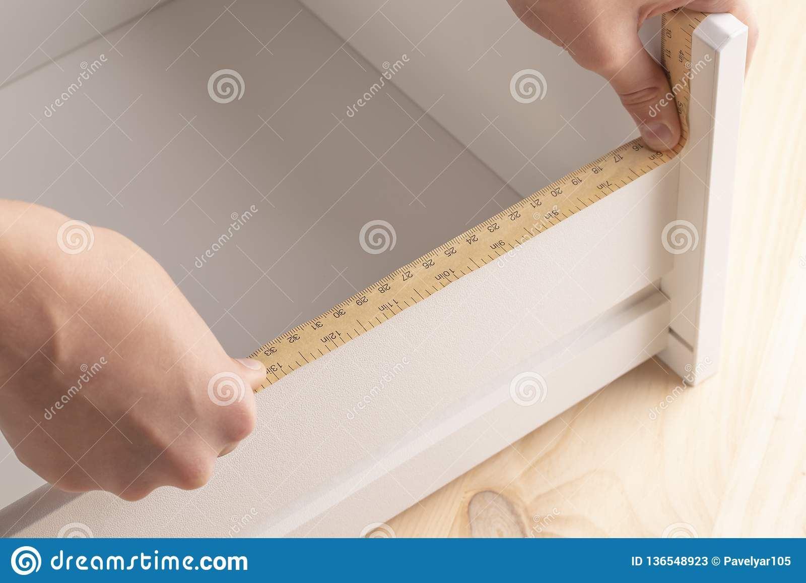 A young man measures the shelves with a measuring tool