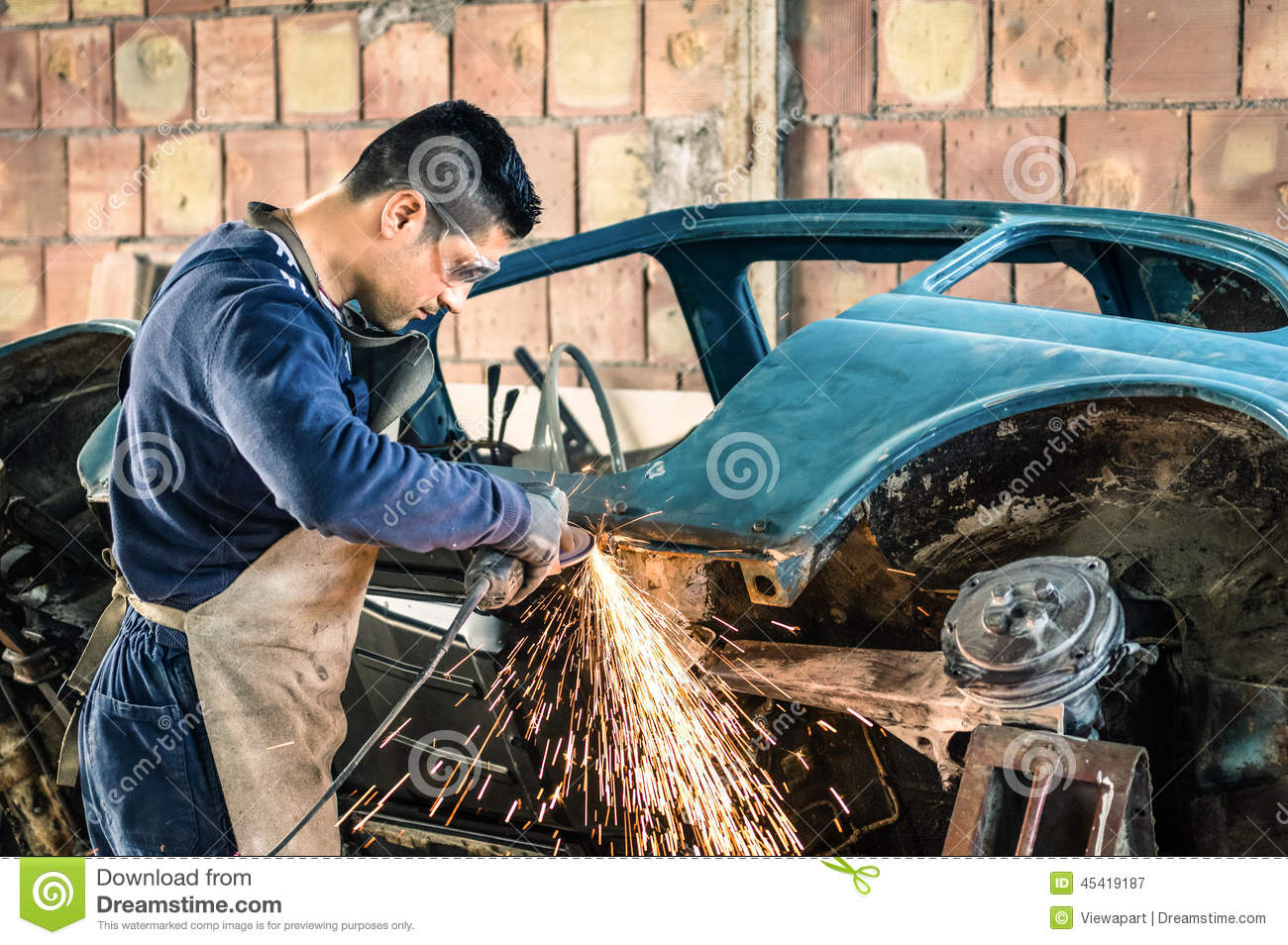 Young man mechanical worker repairing an old vintage car