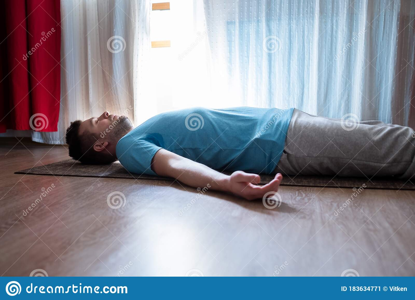 Young Man Meditating On A Floor And Lying In Shavasana ...