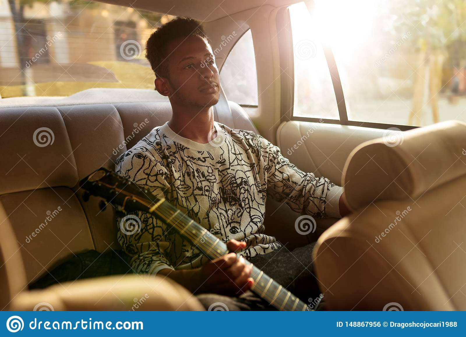 Young man multi race sitting on the back seat in the car. A singer holding a guitar while traveling inside of taxi.