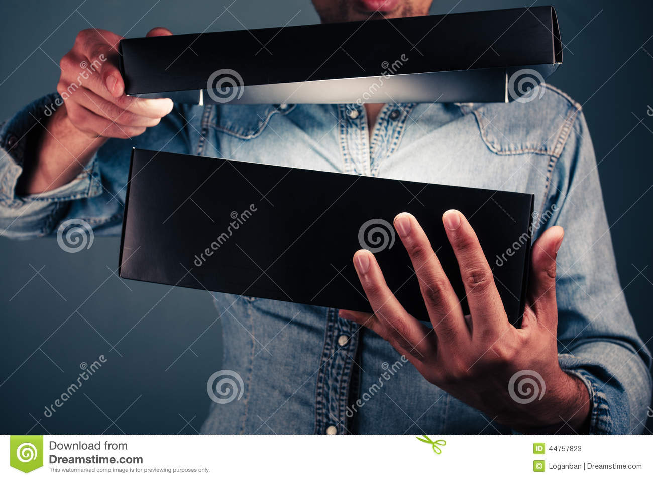Young man opening an exciting box