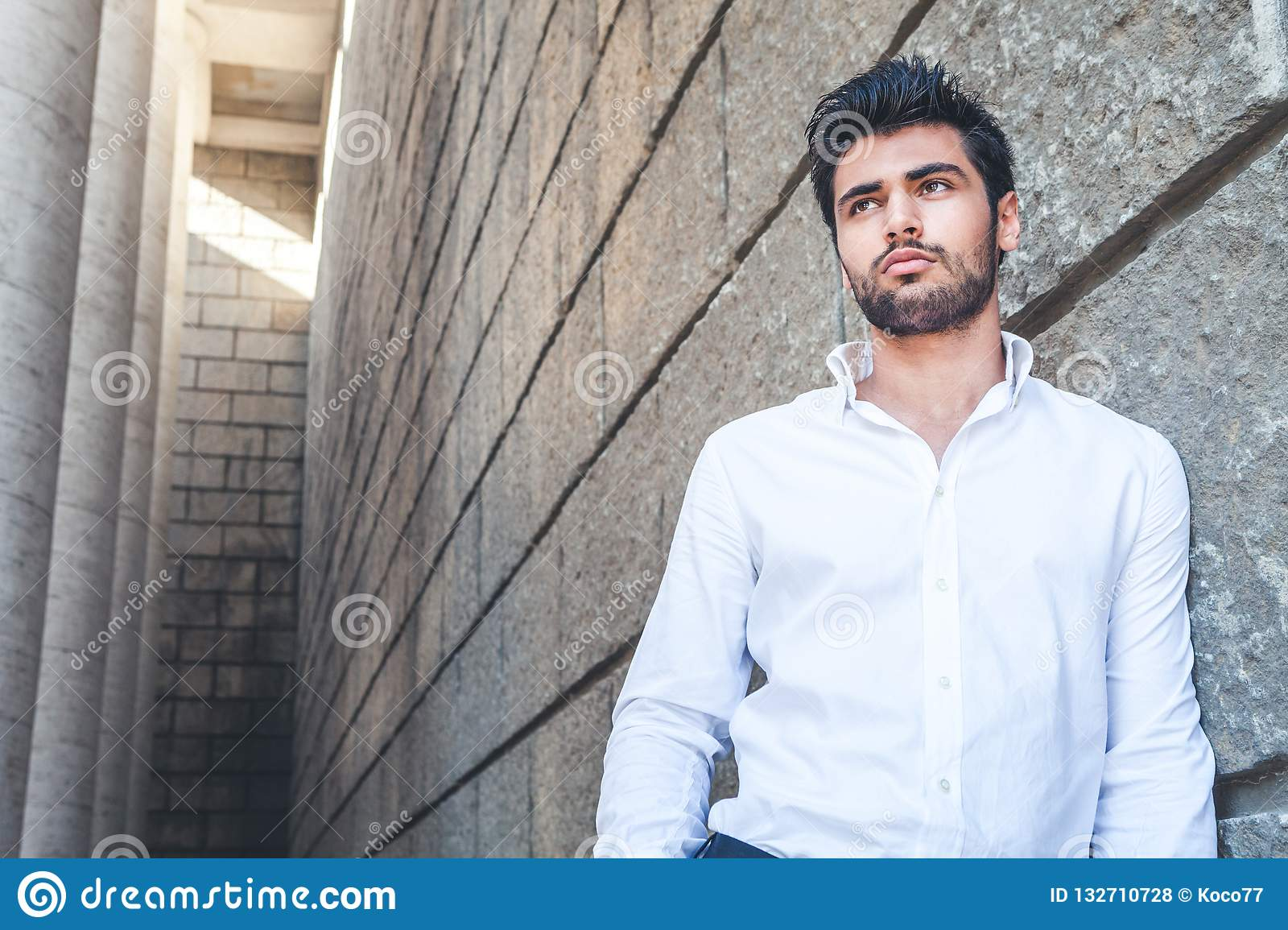 Young man outdoors with free space near. White shirt, fashionable hair and beard.