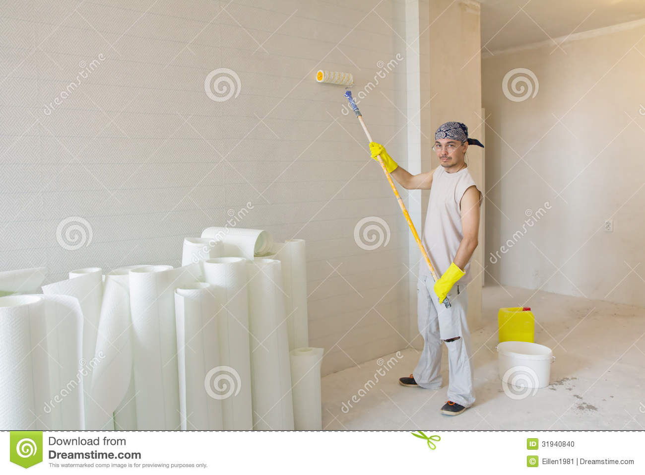 Young man with painting roller painting wallpaper stock - Deco avec papier peint ...