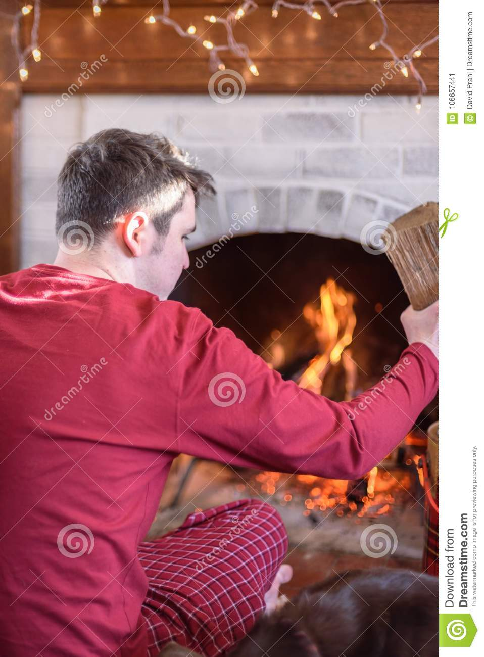 Young Man Starting Fire In Fireplace On Winter Morning Stock Image