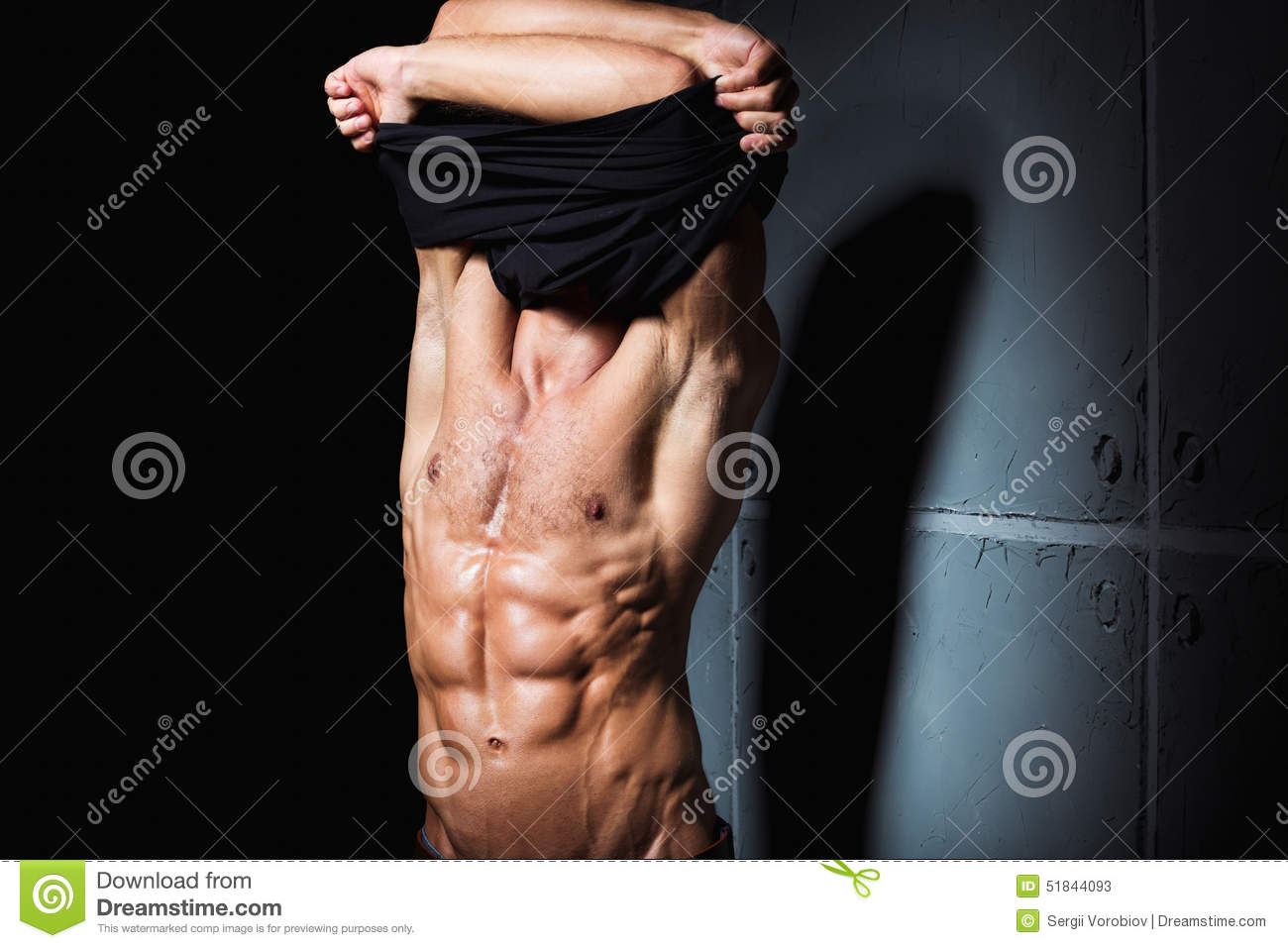 Young man with perfect body stripping