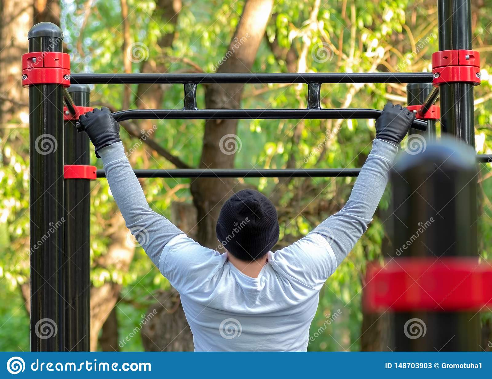 A young man performs a sports exercise pulling on the simulator crossbar. Outdoor training develops the strength of the back