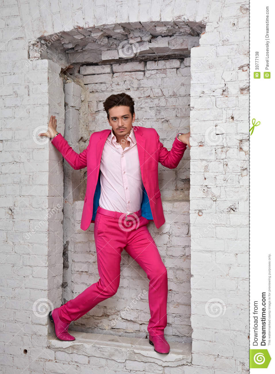 Young Man In Pink Suit And Shoes Stands With In Wall