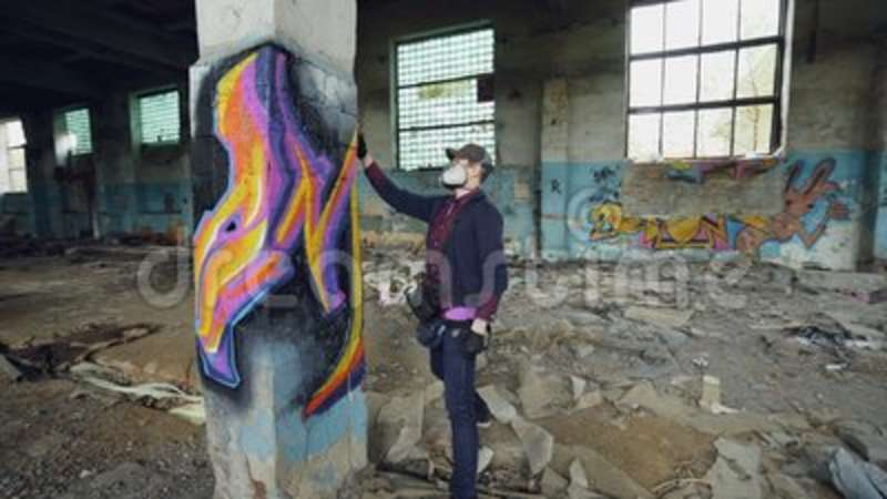 Young man professional graffiti painter is working inside abandoned  building, he is painting with spray aerosol paint on