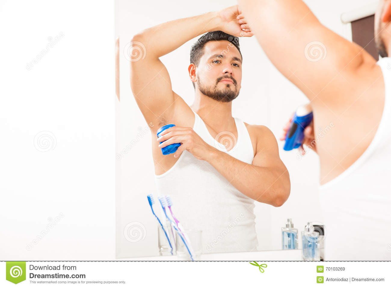 Young Man Putting On Deodorant In The Bathroom Stock Image