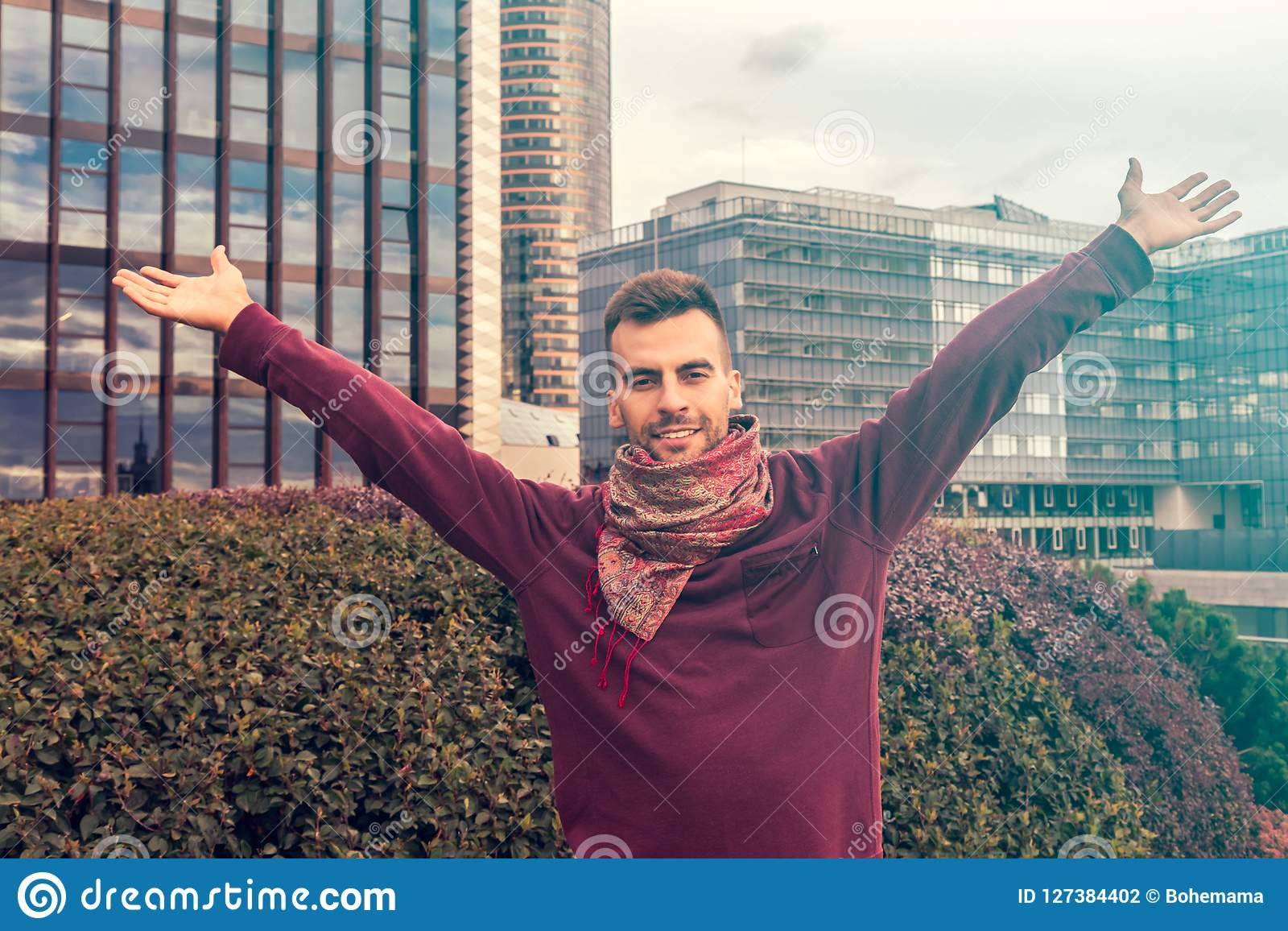 A young man raising his arms, open palms in the modern city center - happy, success and achievement concepts