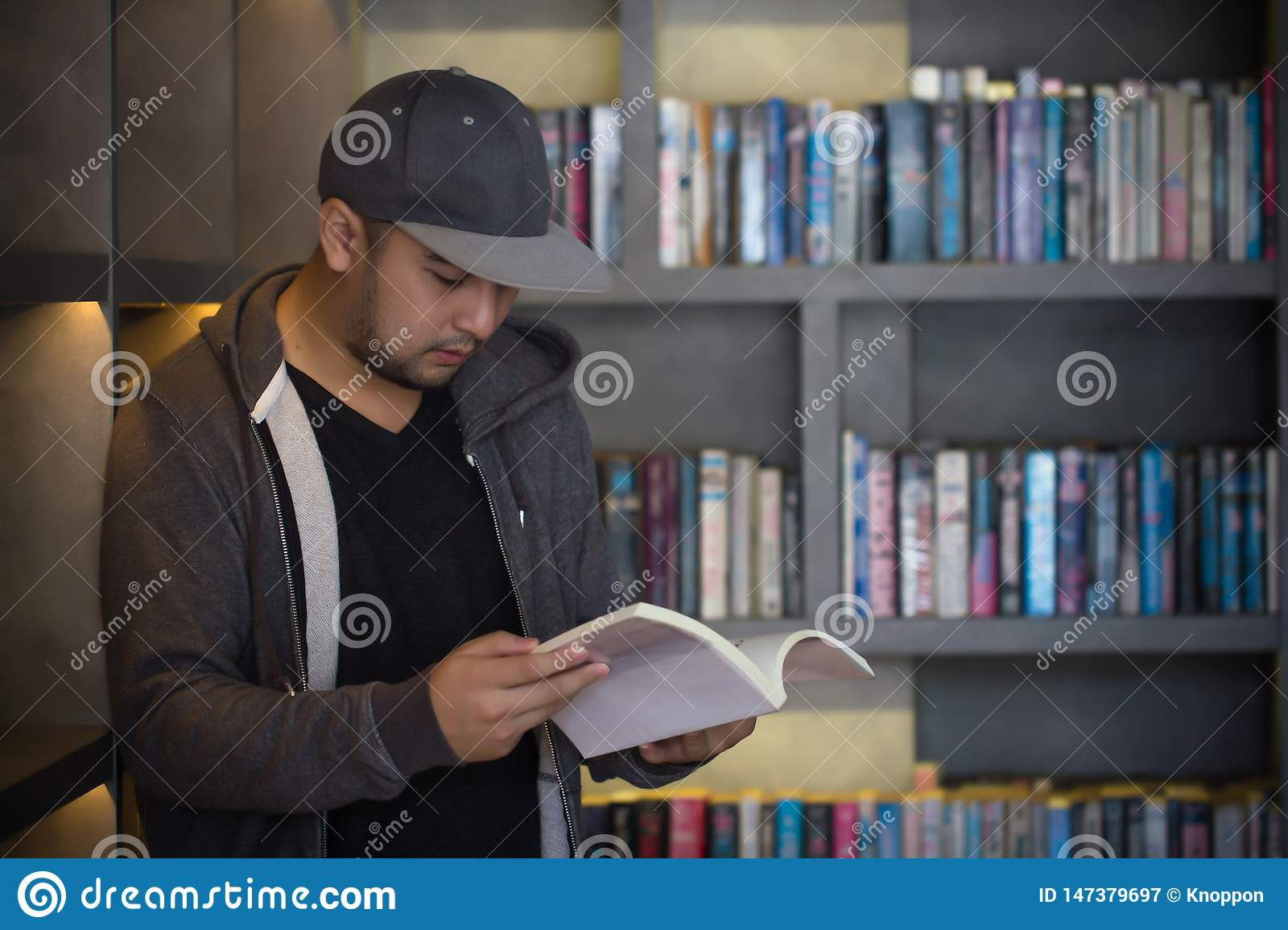 Young man reading book in library. Student in college study from book, knowledge in university concept. Study hard for exam.