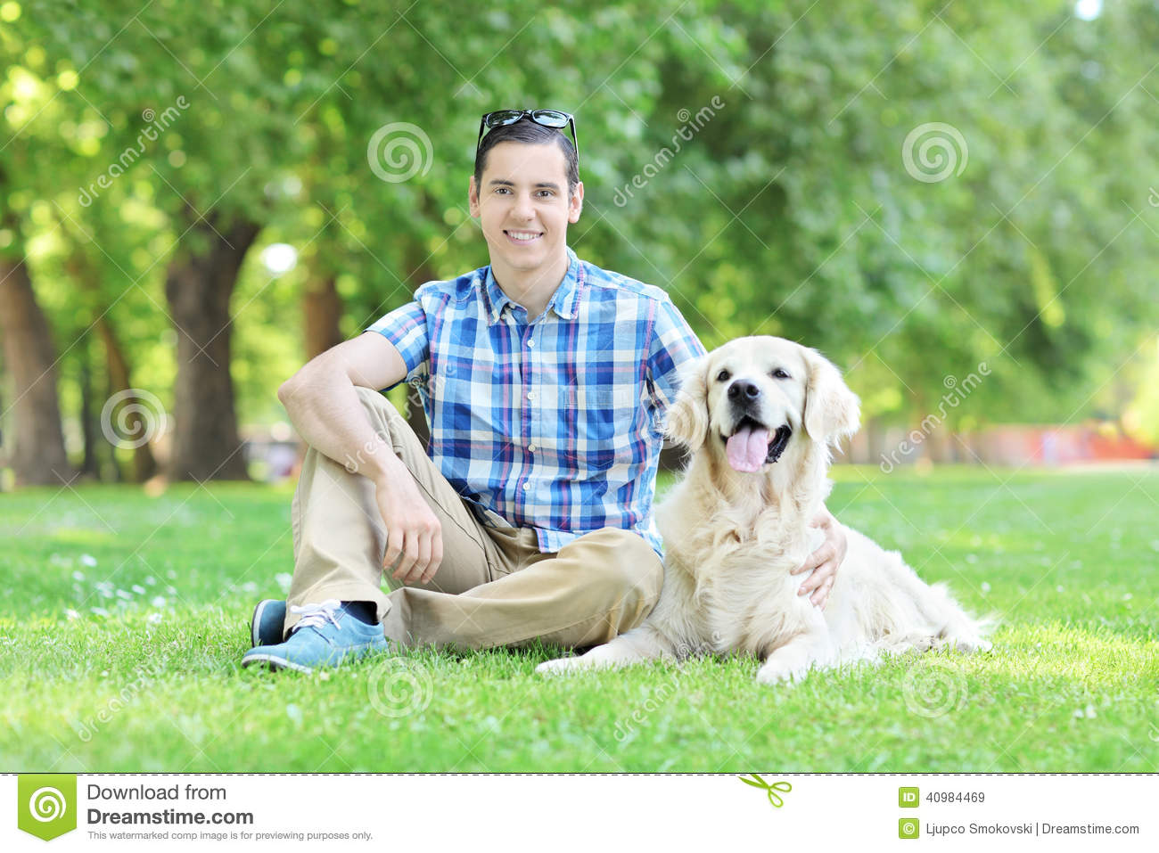 Young man relaxing in park seated with his dog