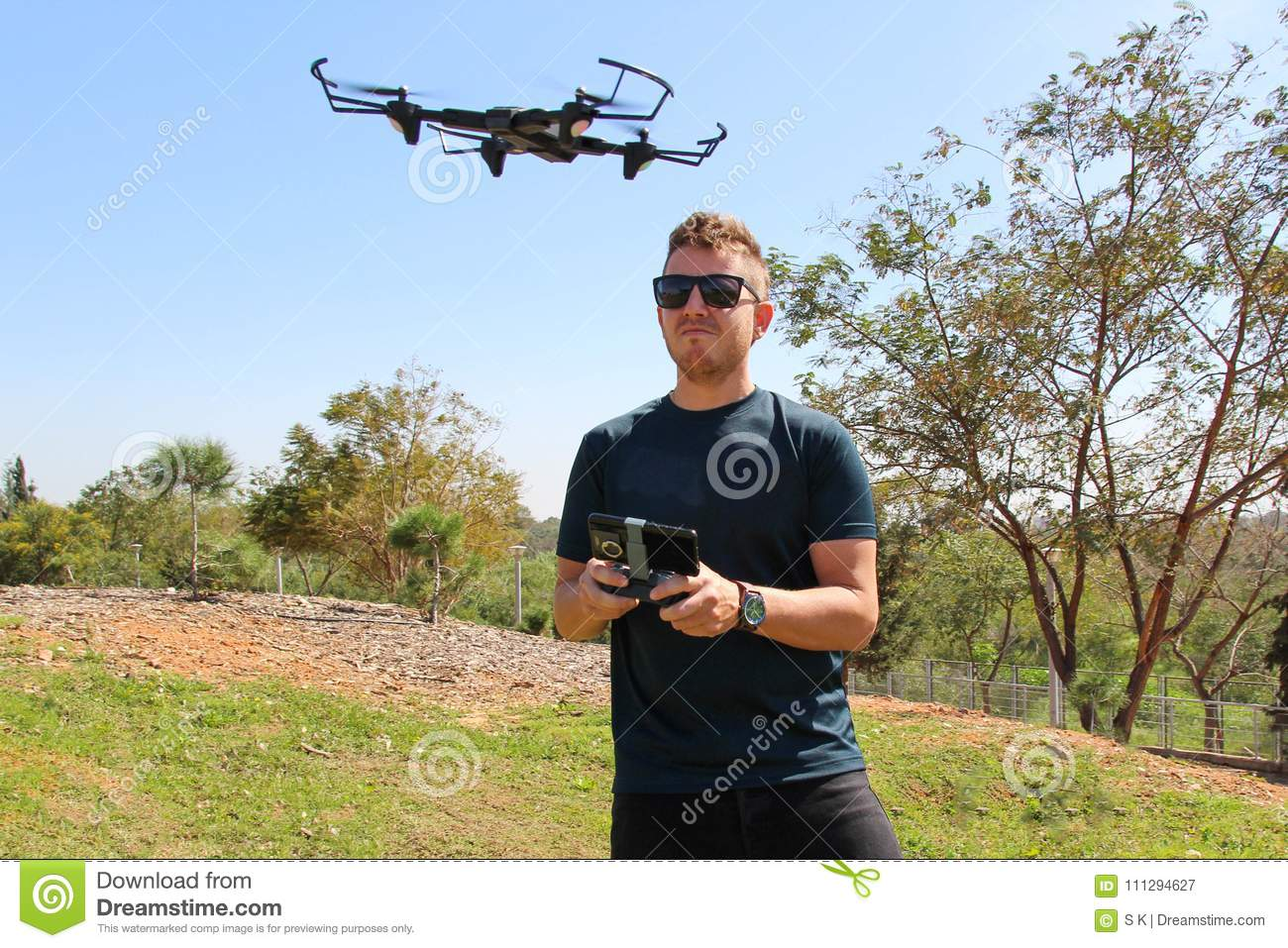 Young man with remote control cell phone flying drone. Sunny green nature