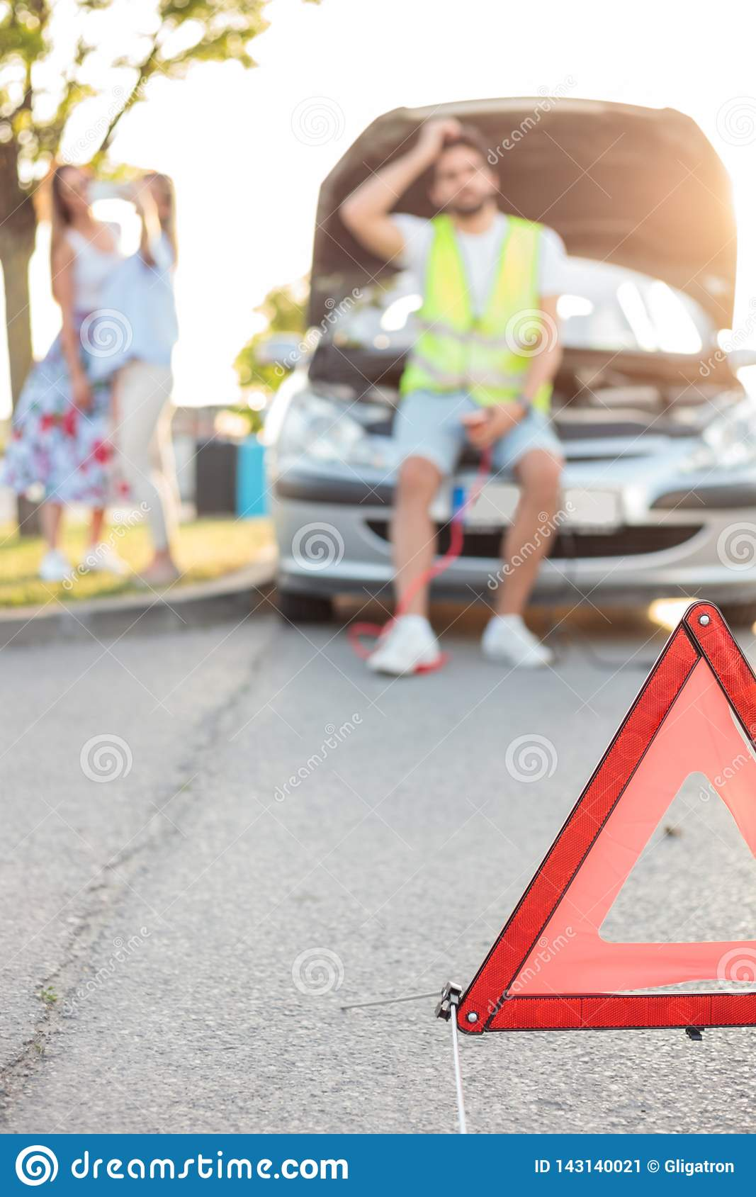 Young man repairing a broken car by the side of the road. Selective focus on emergency triangle in foreground