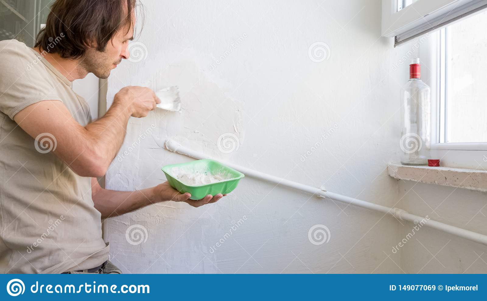 Young man repairing wall at his apartment, applying plaster mix on the wall