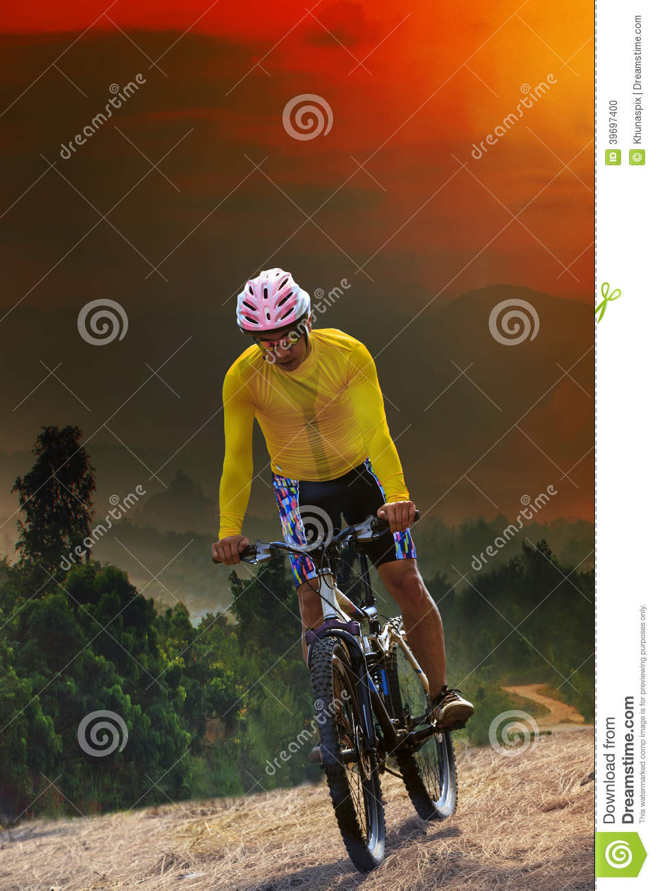 young man riding mountain bike bicycle crossing mountain hill jungle track with dusky sky scene use for out door sport and