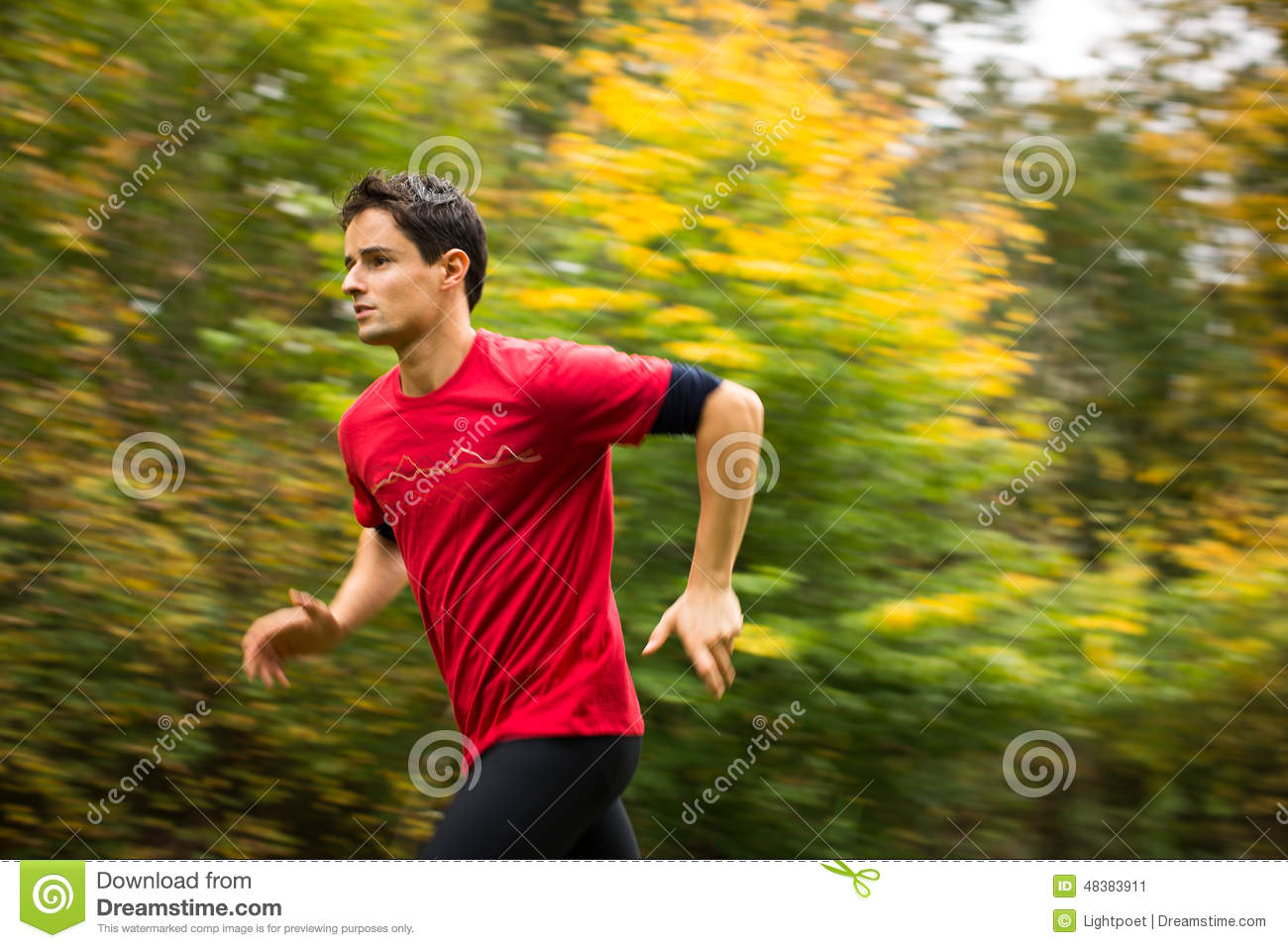Young man running outdoors in a city park on a fall/autumn day