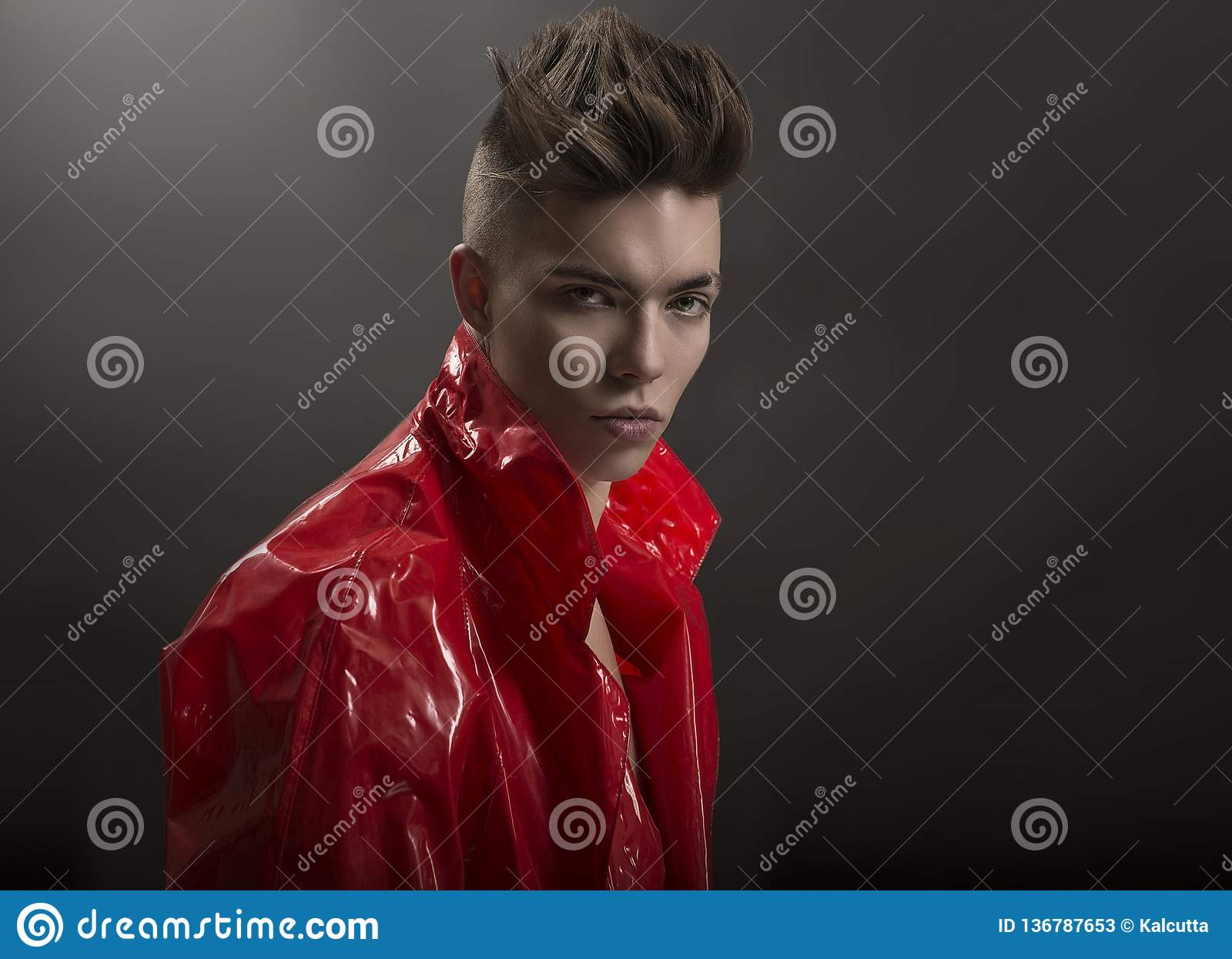 Young man`s portrait. Stylish handsome Guy in fashionable red Long lacquer raincoat, Close-up