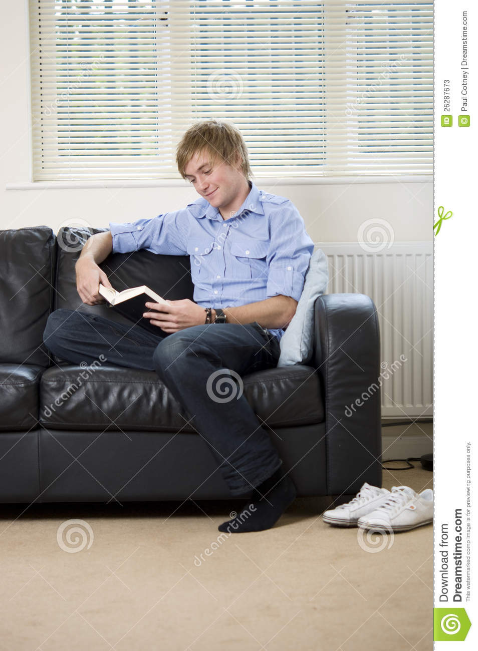Young Man Sat On A Sofa Reading A Book