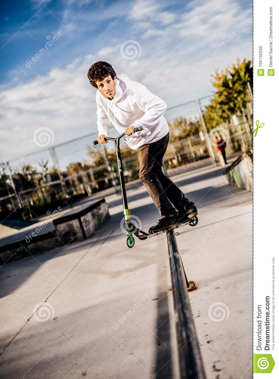 Young man with scooter making a Grind on Skatepark