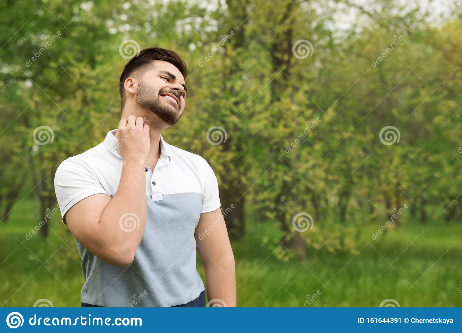 Young man scratching neck outdoors. Seasonal allergy