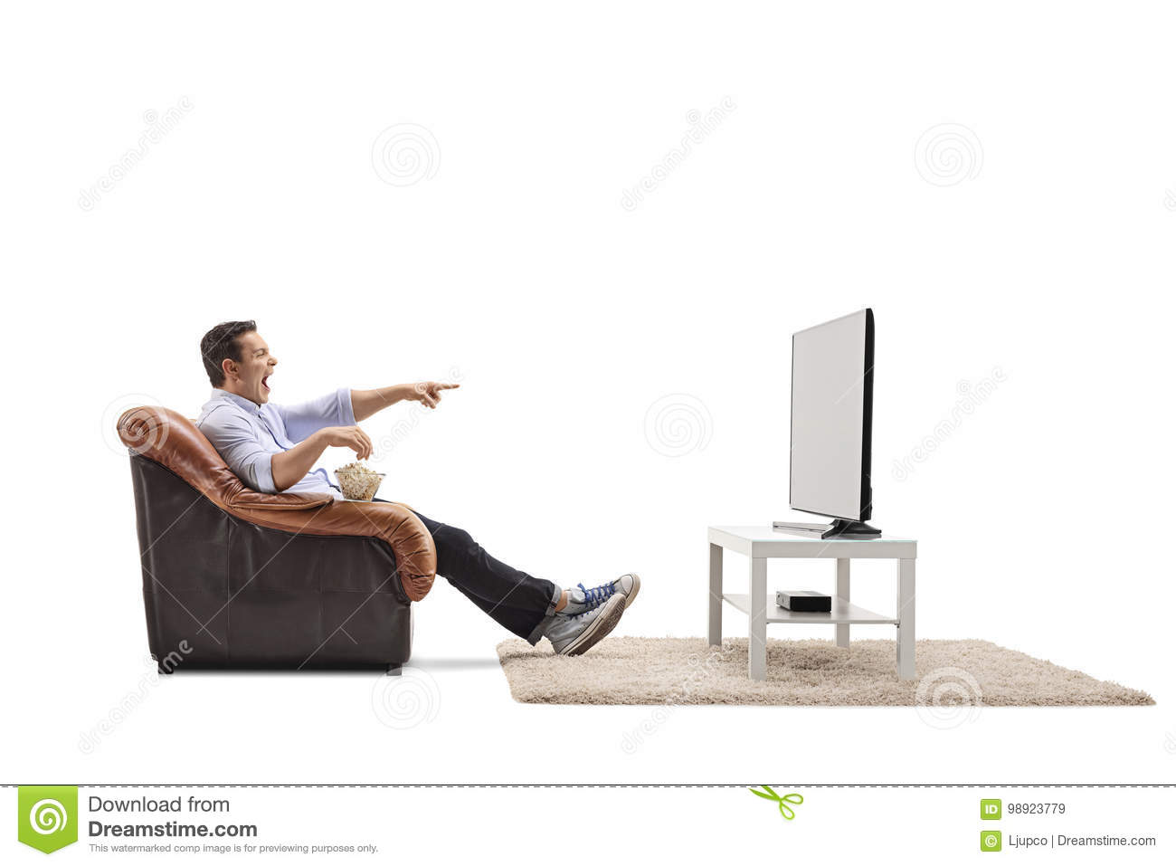 Young man seated in an armchair watching television and laughing