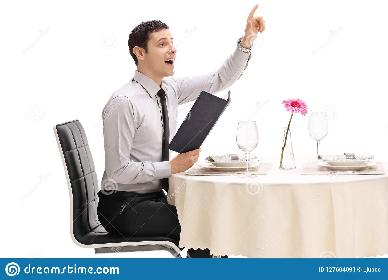 Young man seated at a restaurant table calling the waiter