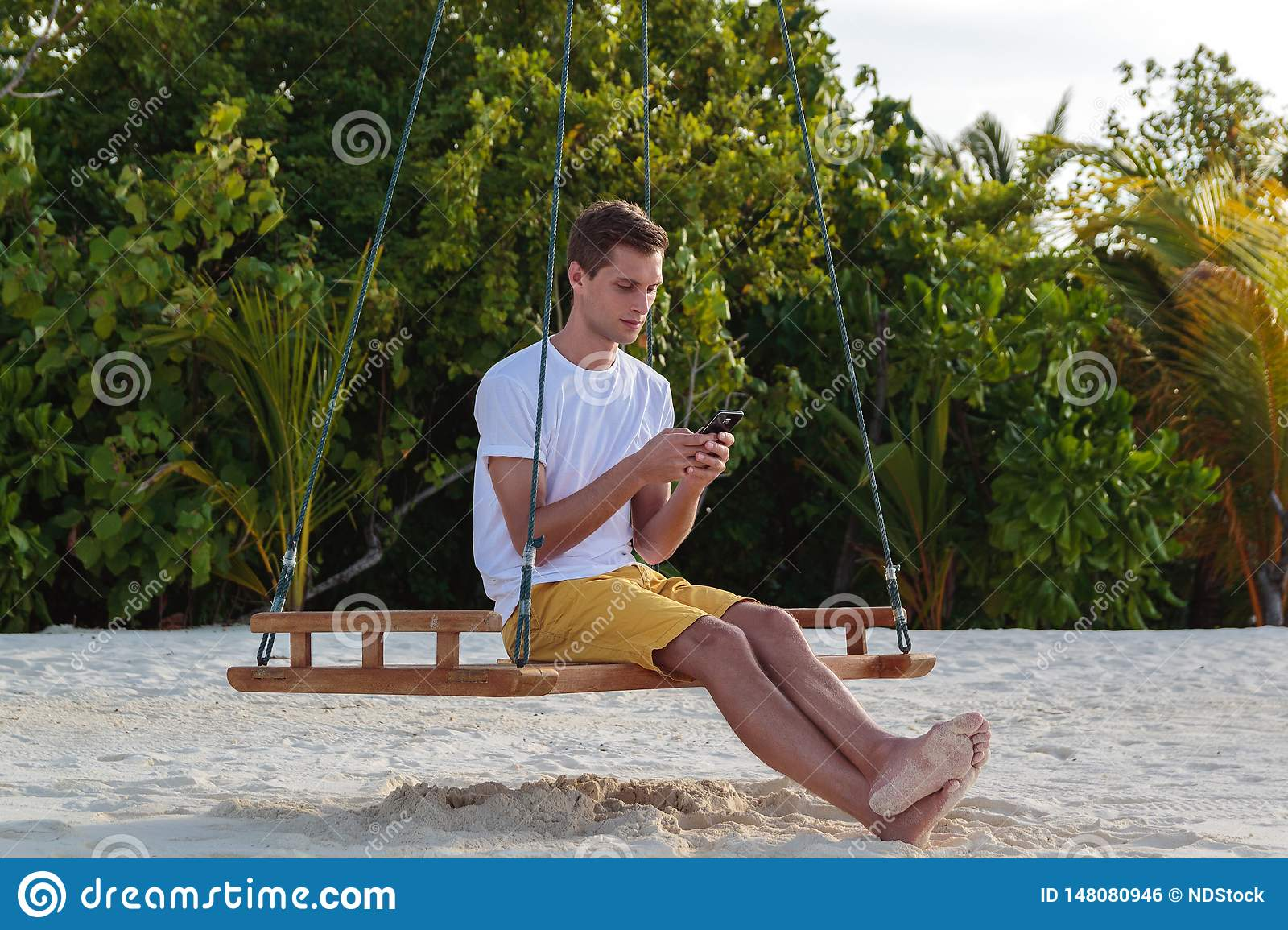 Young man seated on a swing and using his phone. White sand and jungle as background