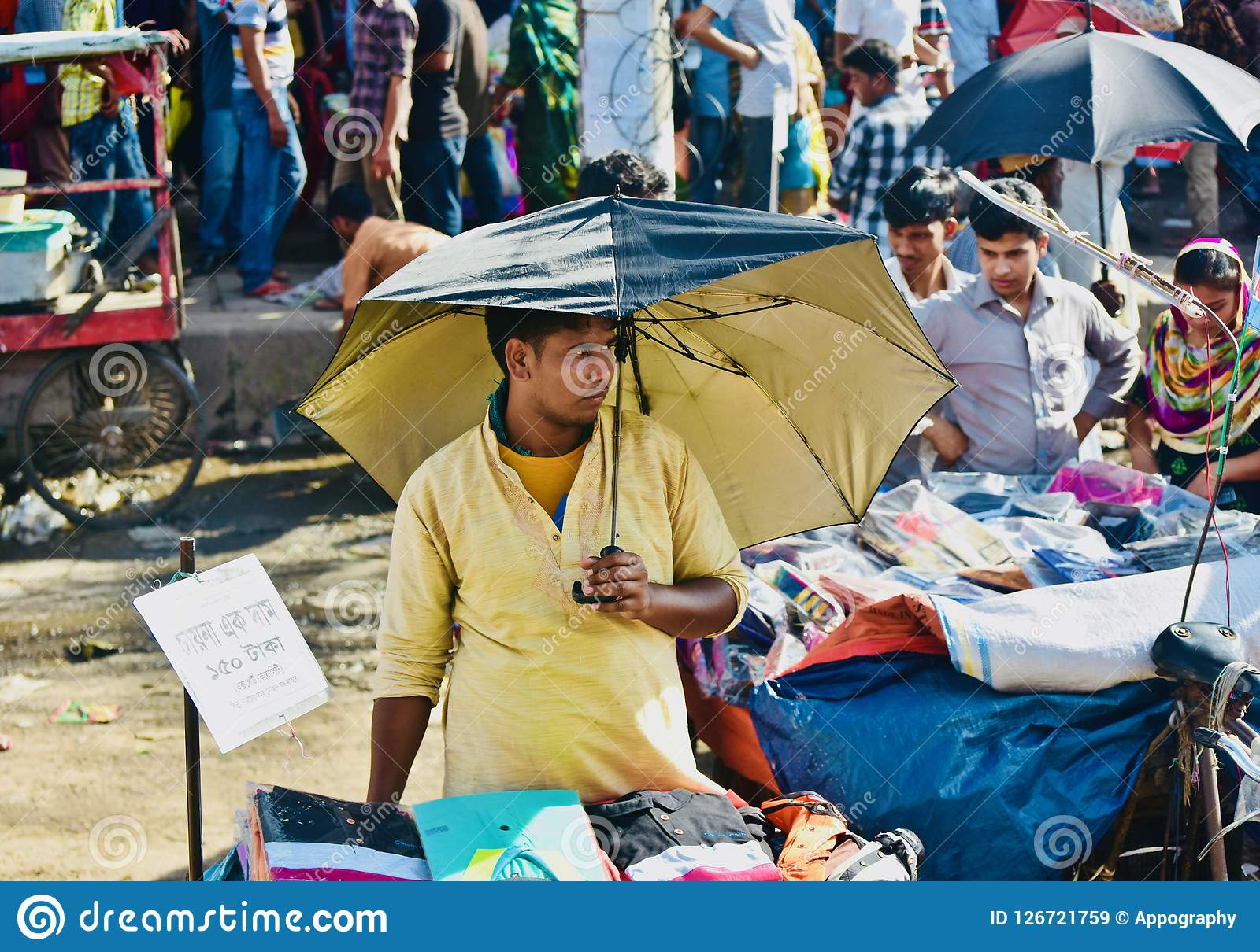 Young street seller is selling garments product in the road unique photo