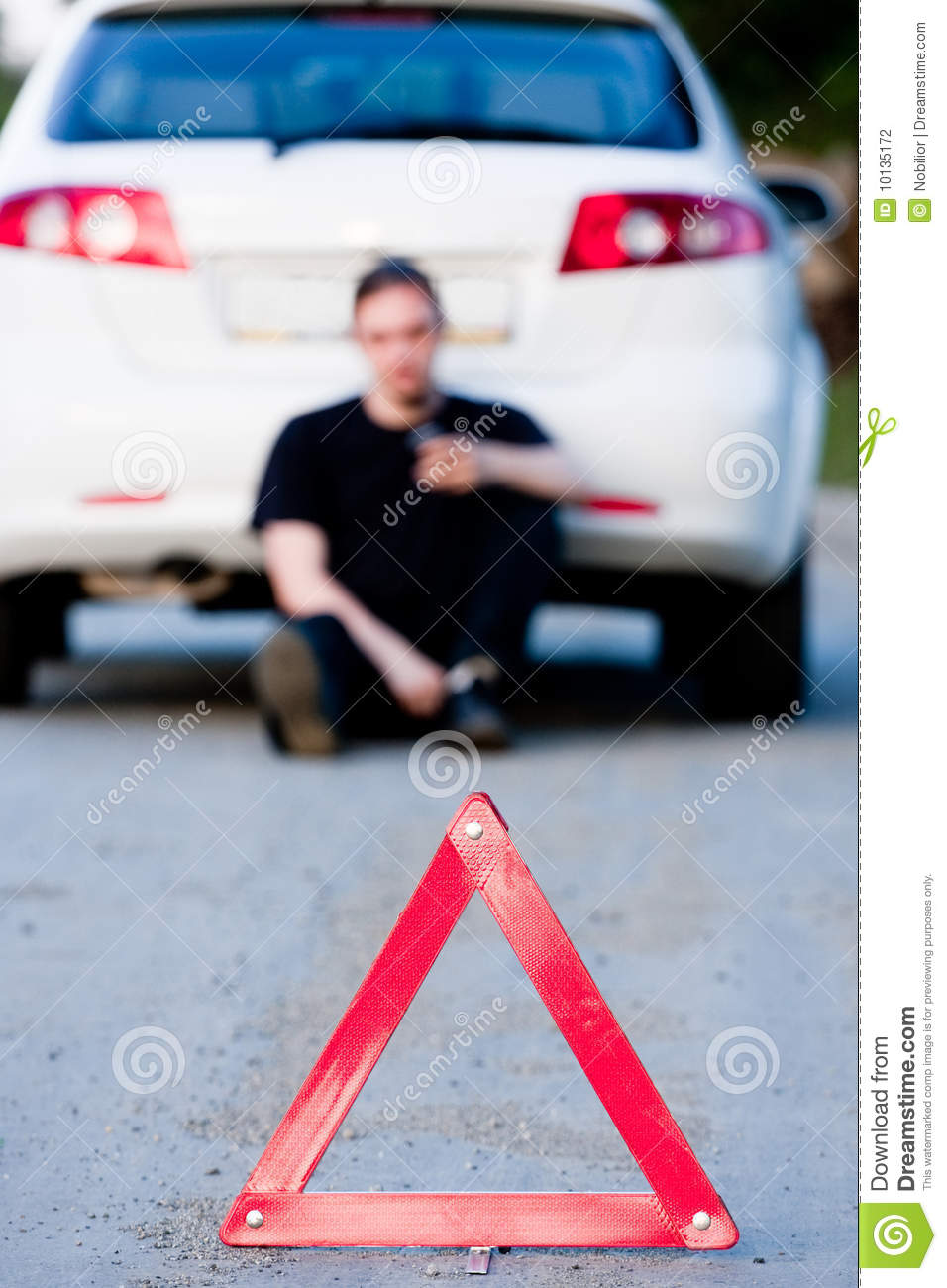 Young man sends an sms sitting by a white car