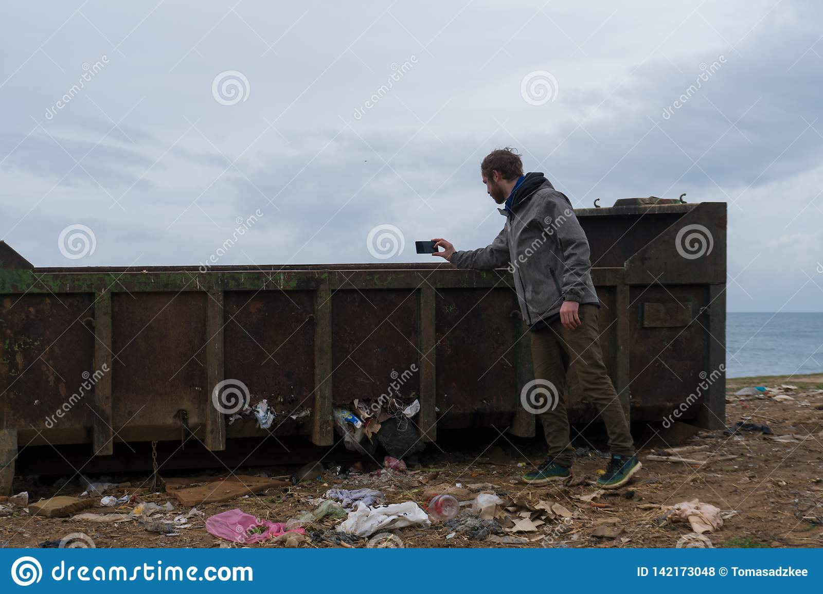 Young Man shooting the garbage Container with Smartphone. Littered Environment