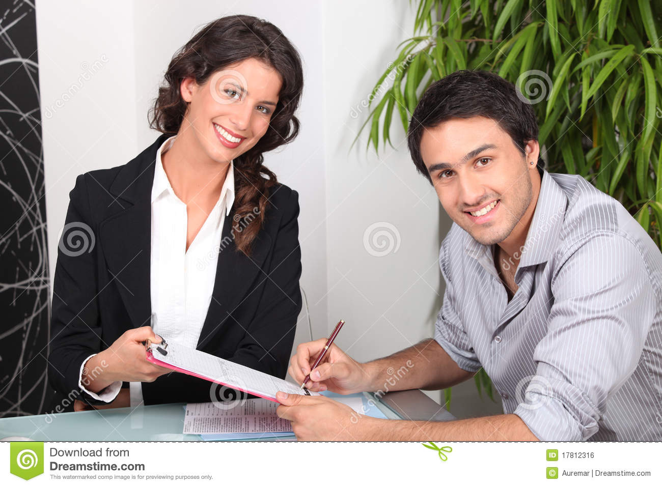Young man signing document and young woman smiling