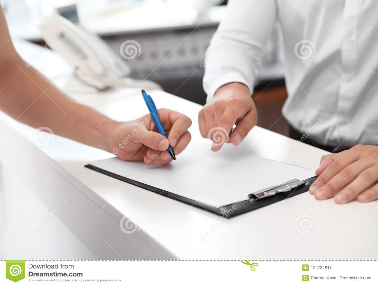 Young man signing documents in salon