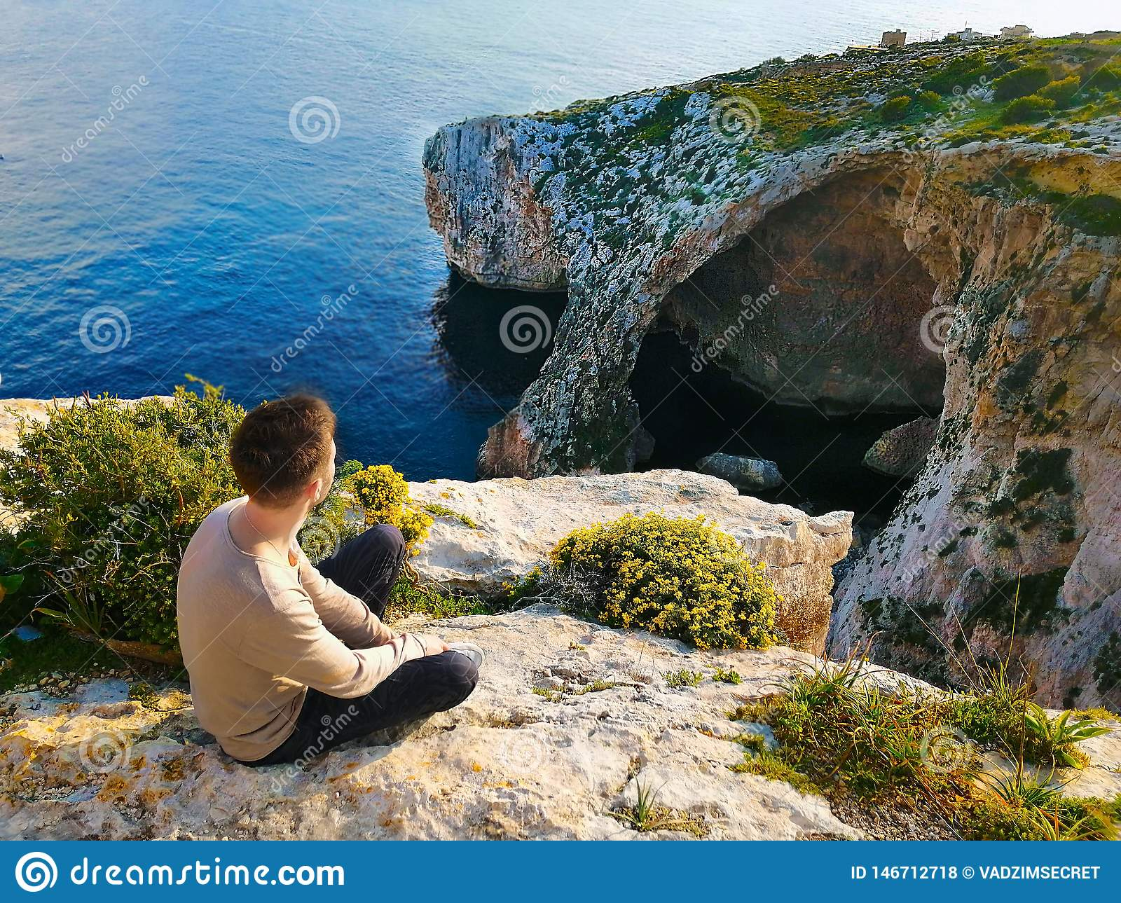 Young man sits on the edge of a cliff and admires the sea and stones