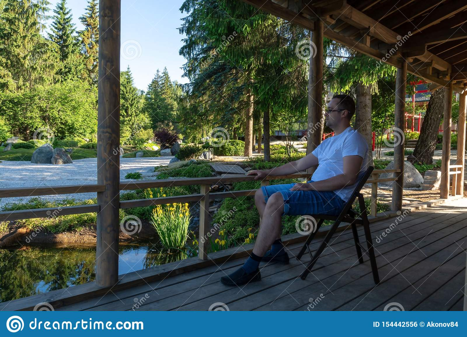A Young Man Sits On A Folding Chair On A Wooden Veranda At Dawn And Looks Ahead Stock Photo ...
