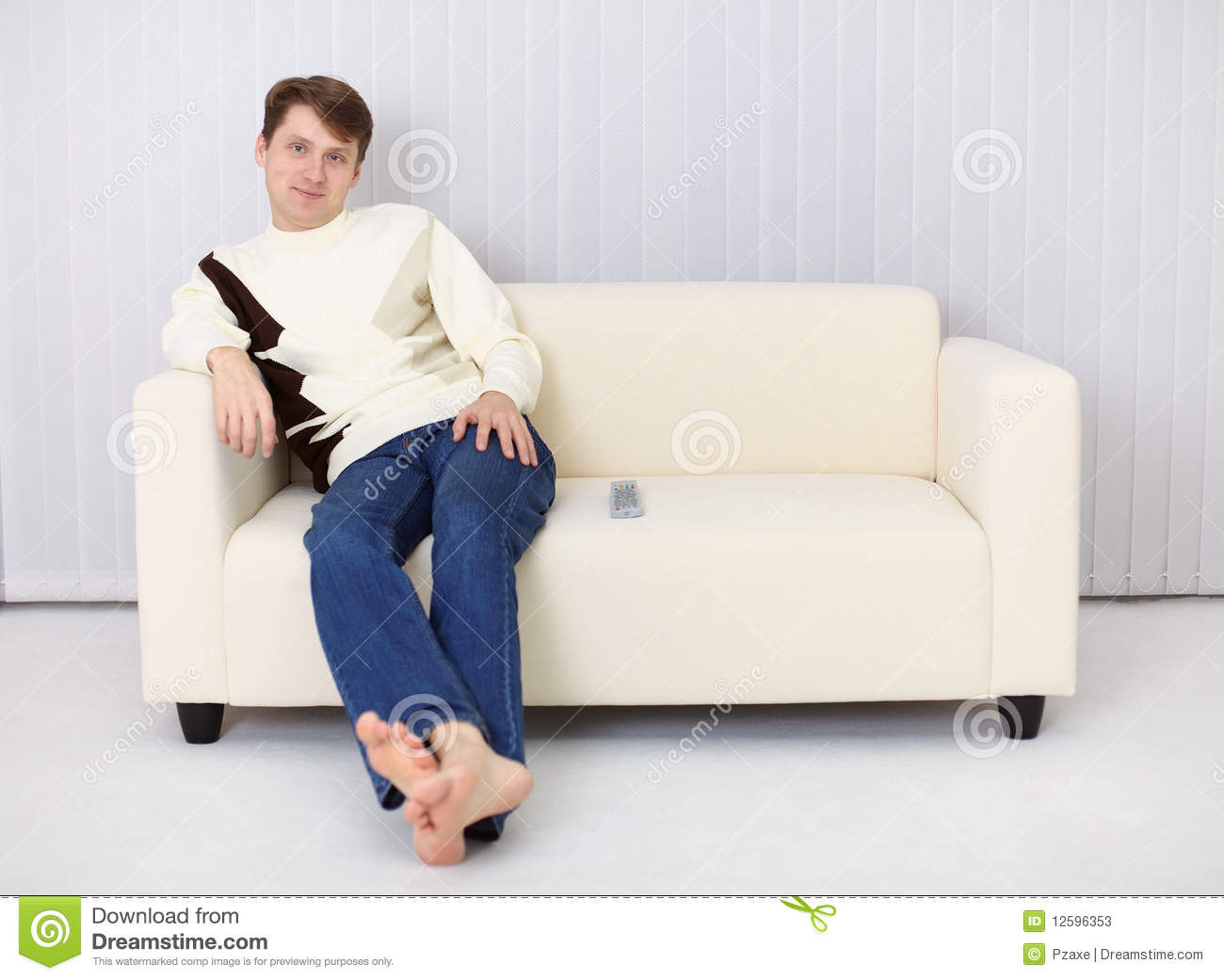 young man sits on sofa and has rest stock photos image 12596353. Black Bedroom Furniture Sets. Home Design Ideas