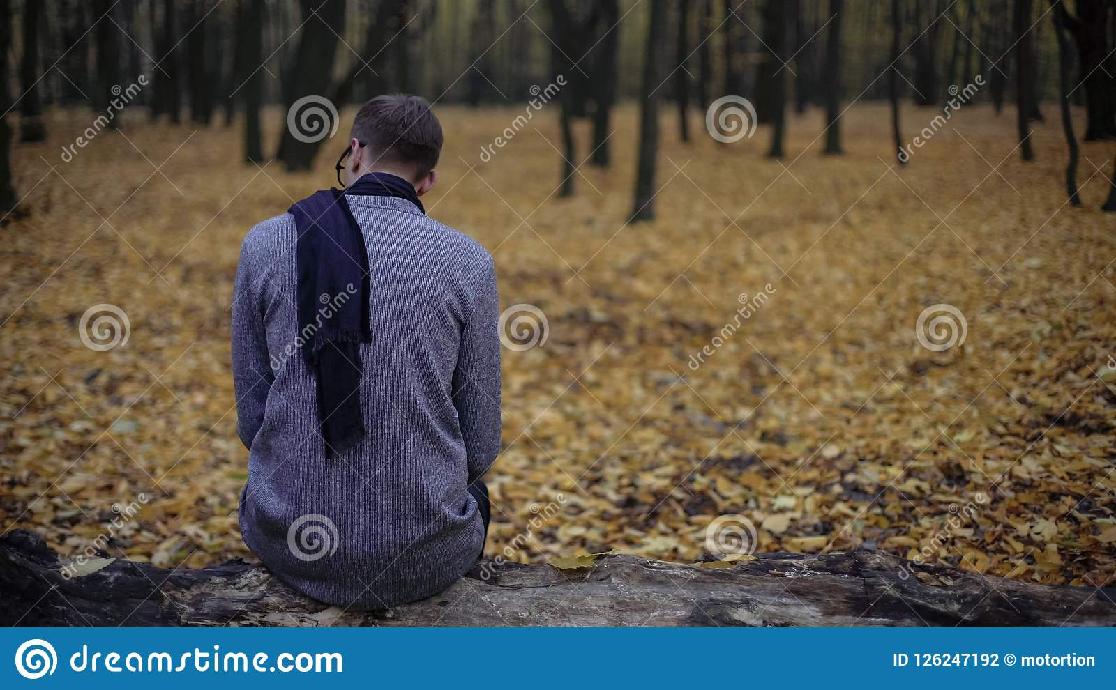 Young man sitting alone in autumn park, feels depression, nostalgia, loneliness