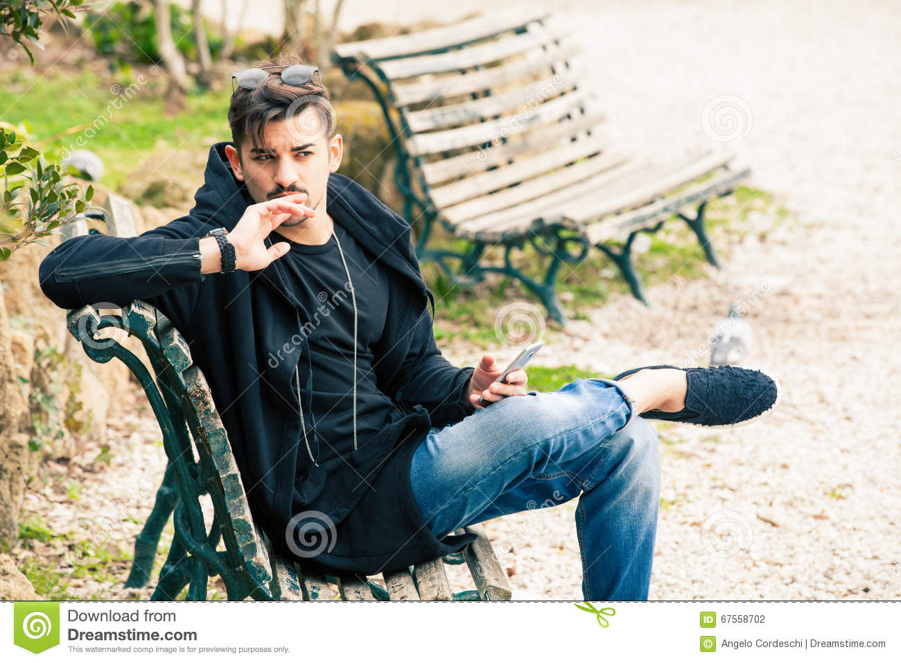 Young Man Sitting On The Bench Waiting With Phone In Hand
